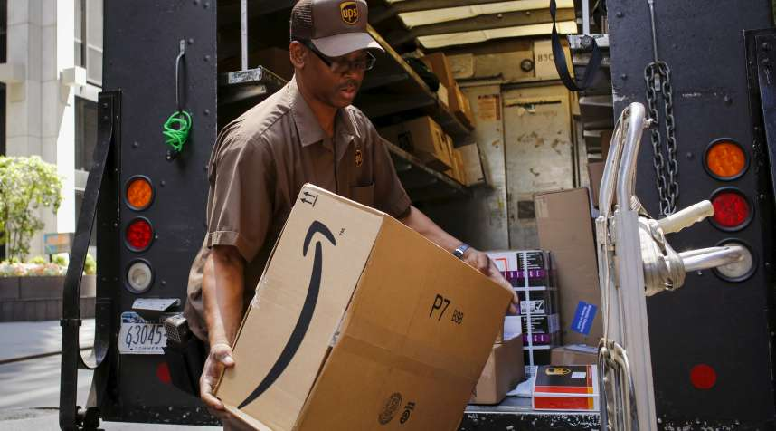 A UPS worker carries an Amazon box to be delivered in New York July 24, 2015.