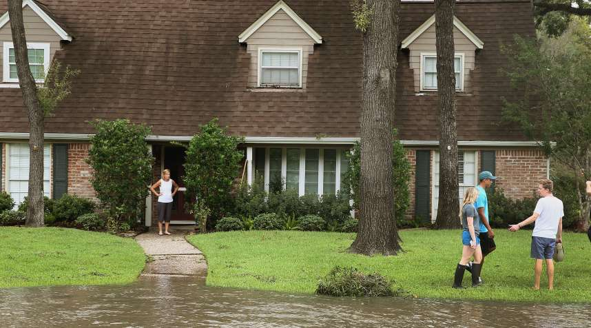 People watch as water continues to rise in their neighborhood following Hurricane Harvey on August 30, 2017 in Houston, Texas.