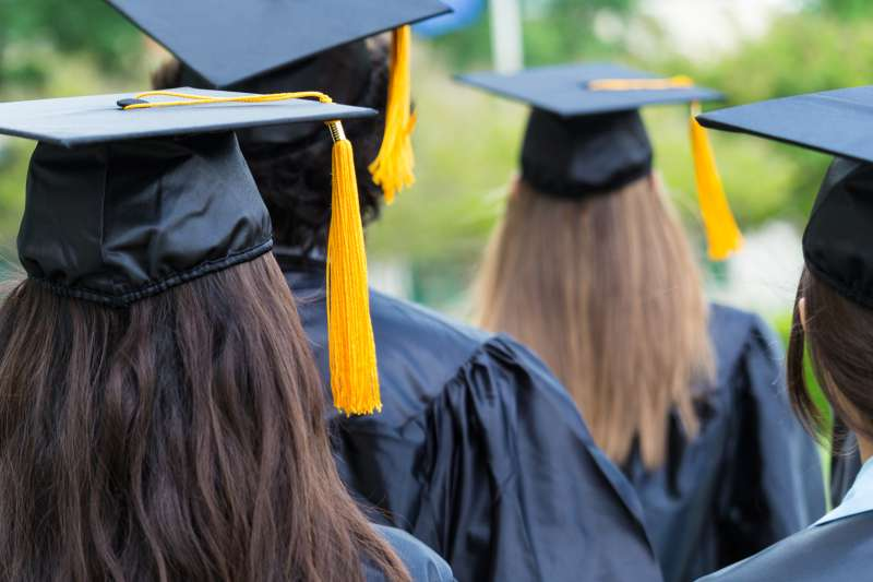 Group of students wearing graduation caps and gowns are walking on campus lawn