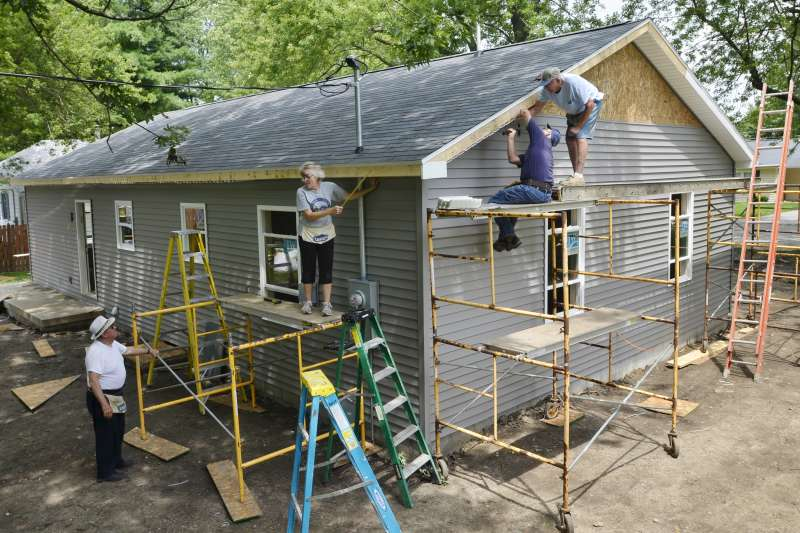 Volunteers, including, from left, Pedro Nieto, Rita Baker, Marty Kemp and Galen Clark, work on the Habitat for Humanity home being built in Sweetser, Ind., on July 12, 2017.