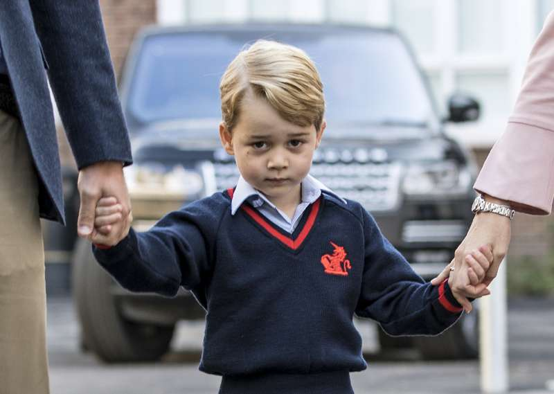 Britain's Prince George (C) accompanied by Britain's Prince William (L), Duke of Cambridge arrives for his first day of school at Thomas's school where he is met by Helen Haslem (R) head of the lower school in southwest London on September 7, 2017.