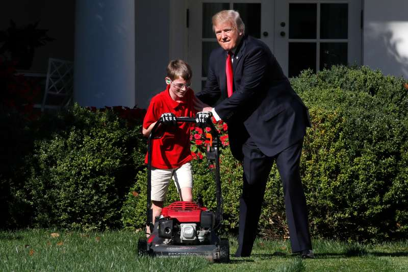 Frank Giaccio, 11, of Falls Church, Va., left, is encouraged by President Donald Trump, Friday, Sept. 15, 2017, while he mowed the lawn in the Rose Garden at the White House in Washington.