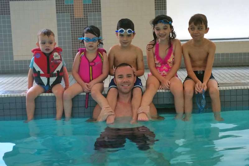 Adrian Crook with his kids in the condo pool.