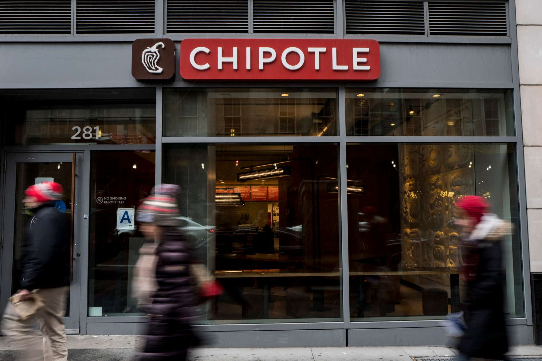 People walk past a Chipotle restaurant on Broadway in Lower Manhattan on Feb. 8, 2016 in New York City.