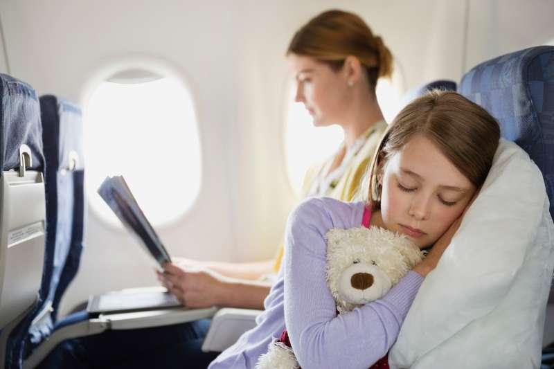 Girl sleeping with stuffed animal in airplane