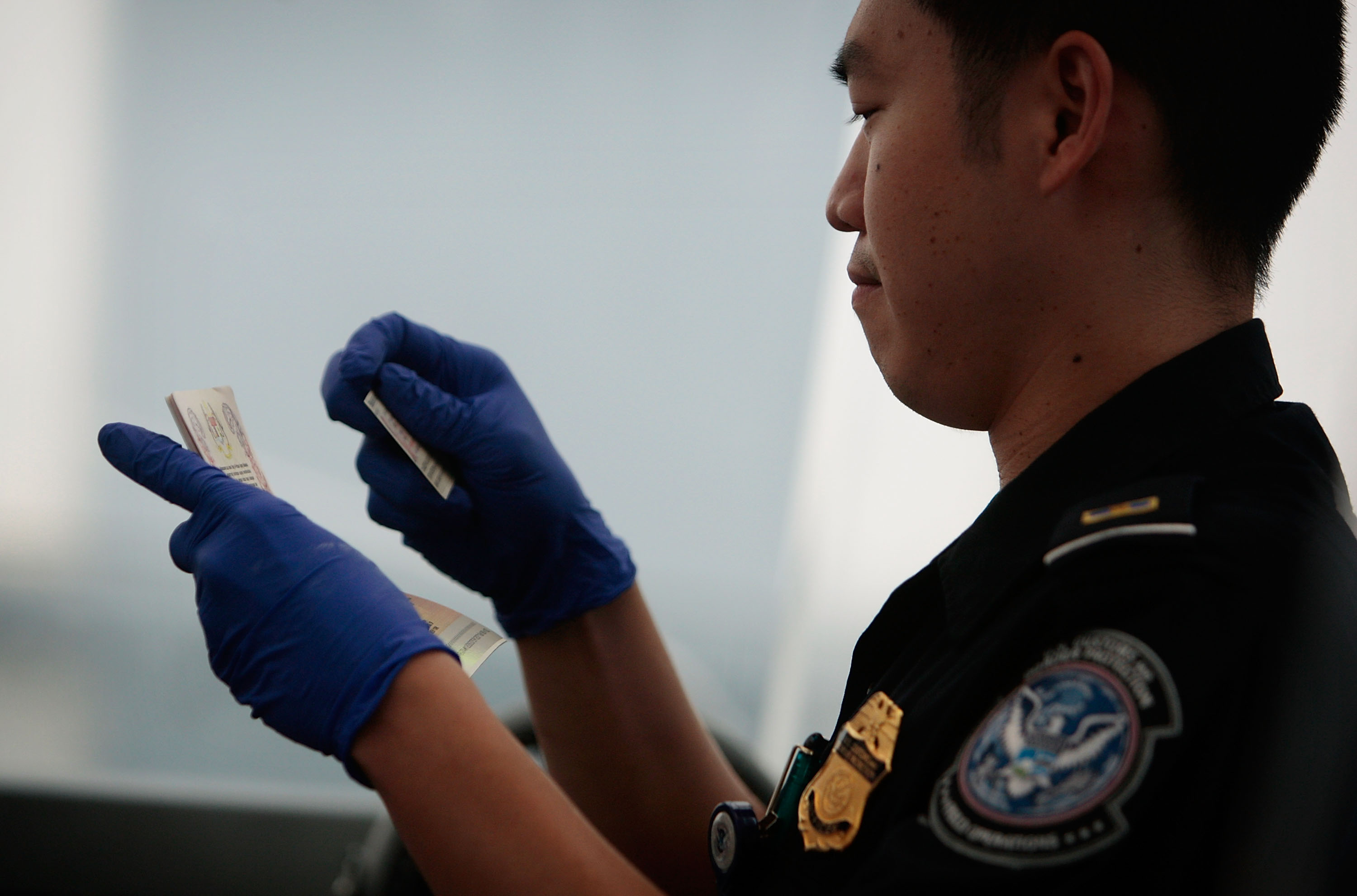 A United States Customs and Border Protection officer checks checks two forms of identification for a traveler arriving from overseas into Newark International Airport.
