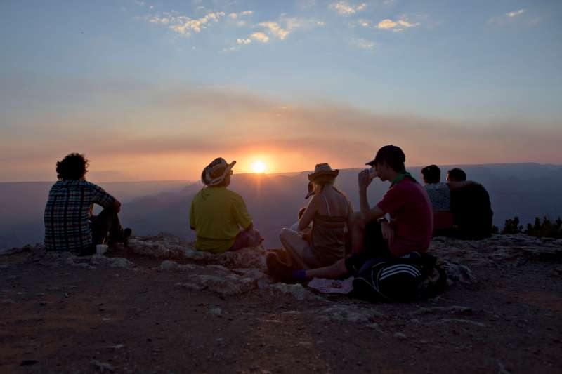 Visitors watch the sun set over the Grand Canyon at the Desert View observation point in Grand Canyon National Park in Grand Canyon, Arizona, U.S., on Thursday, June 25, 2015. The Grand Canyon has seen a 20 percent increase in visitation through the first quarter of this year, according to a park spokesperson. Photographer: Daniel Acker/Bloomberg via Getty Images