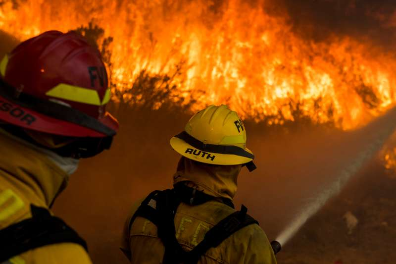 Firefighters from the city of Fountain Valley try to hold back flames from the Canyon Fire 2 along Santiago Canyon Road  on October 9th, 2017 in Anaheim Hills, California.
