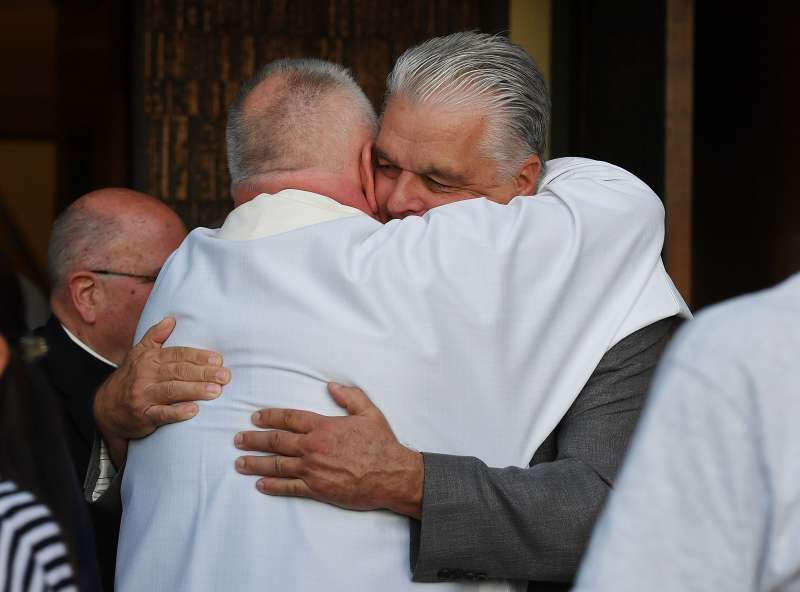 Clark County Commission Chair Steve Sisolak embraces a member of the clergy as he attends a vigil at Guardian Angel Cathedral for the victims of the Route 91 Harvest country music festival shootings on October 2, 2017 in Las Vegas, Nevada.