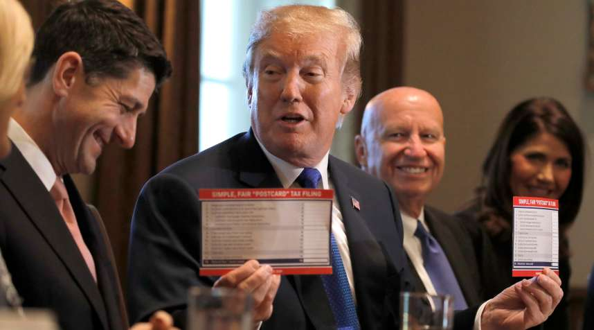 U.S. President Donald Trump holds sample tax forms as he promotes a newly unveiled Republican tax plan with House Republican leaders in the Cabinet Room of the White House in Washington, U.S., November 2, 2017.