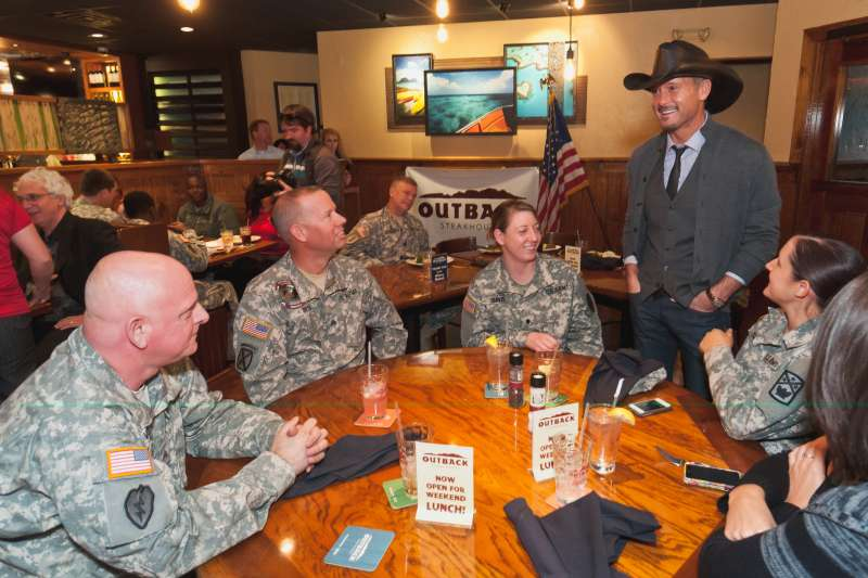 (left to right) Sargent John Davidson, Sargent Kenneth Best, Specialist Lauren Travis, Specialist Hannah Tart and Nichole Cox  speak with Tim McGraw at an Outback Steakhouse.