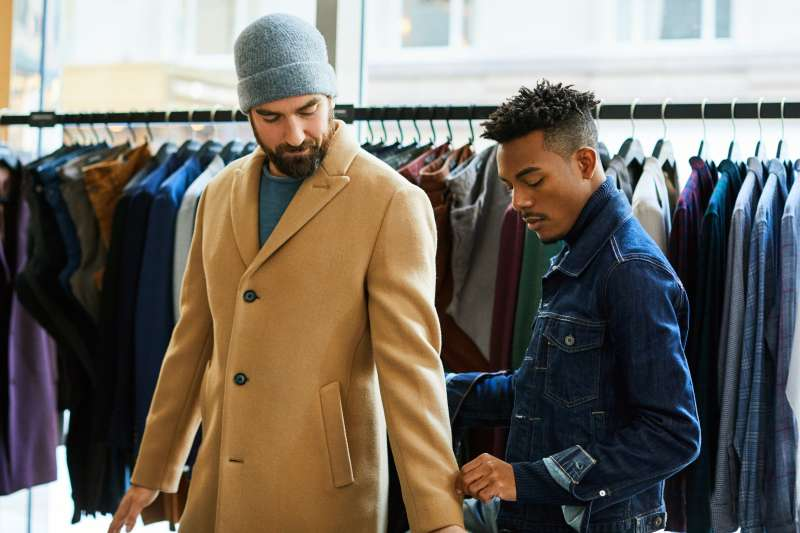 Josh Jones checks the fit of a coat on Tyler Kantor at the Madison Avenue location of Bonobos in New York City