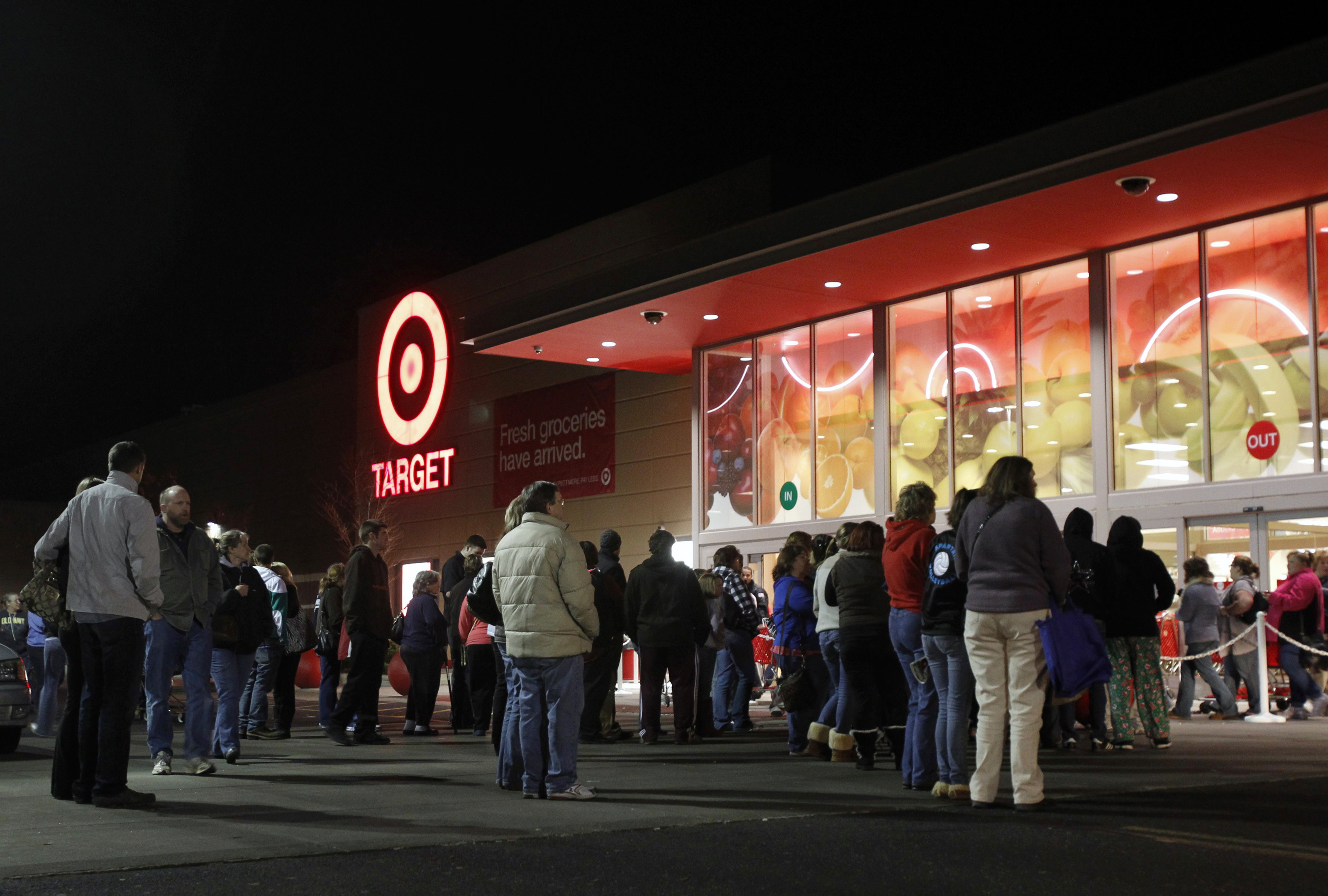 "Shoppers stand outside of a Target store at midnight on ""Black Friday"" as they wait for those who stood in line to enter the store first in Torrington"