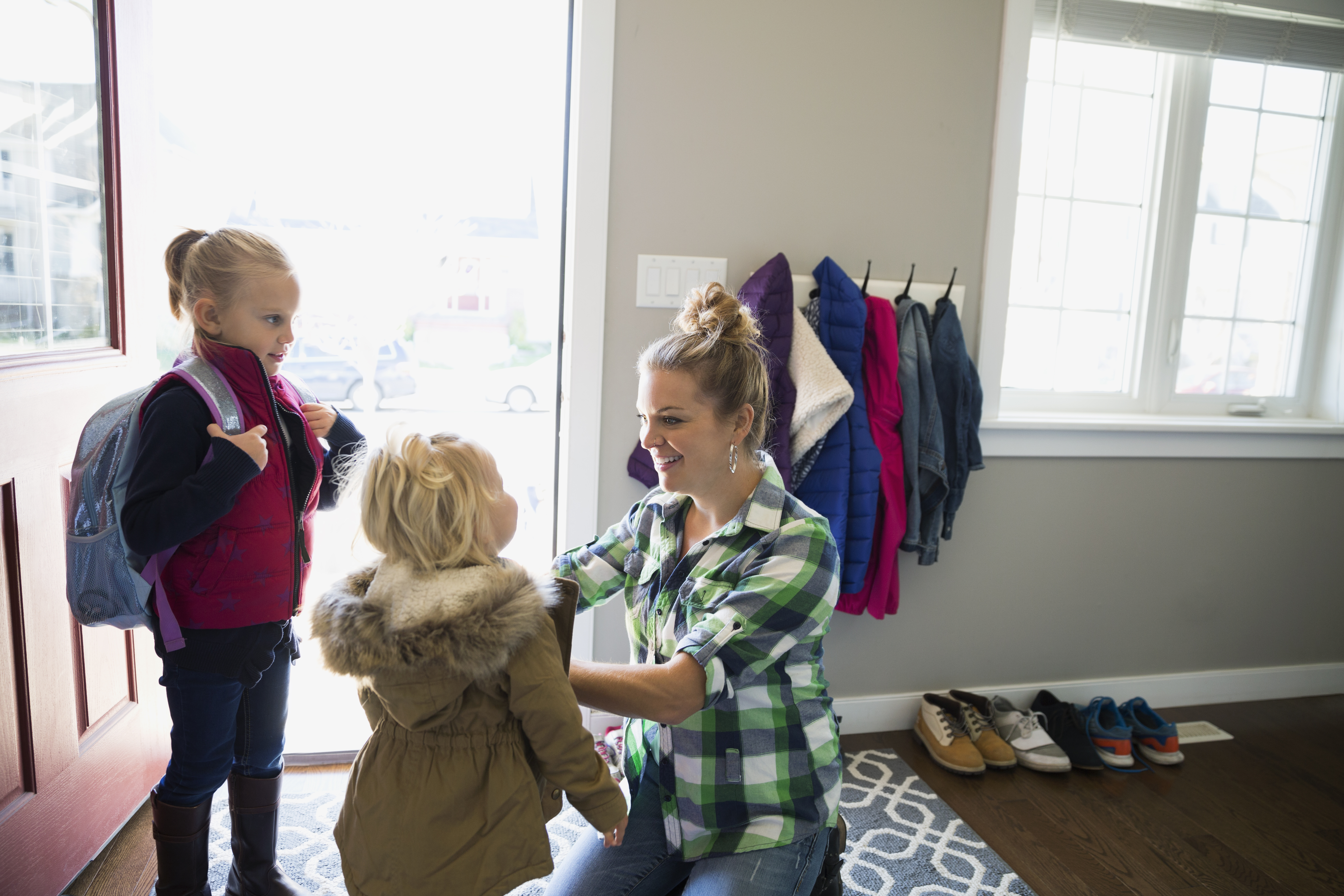 Mother preparing daughters for school at front door