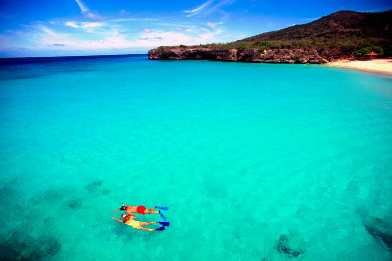 Couple snorkeling in crystal clear water off Knip Beach in Curacao.