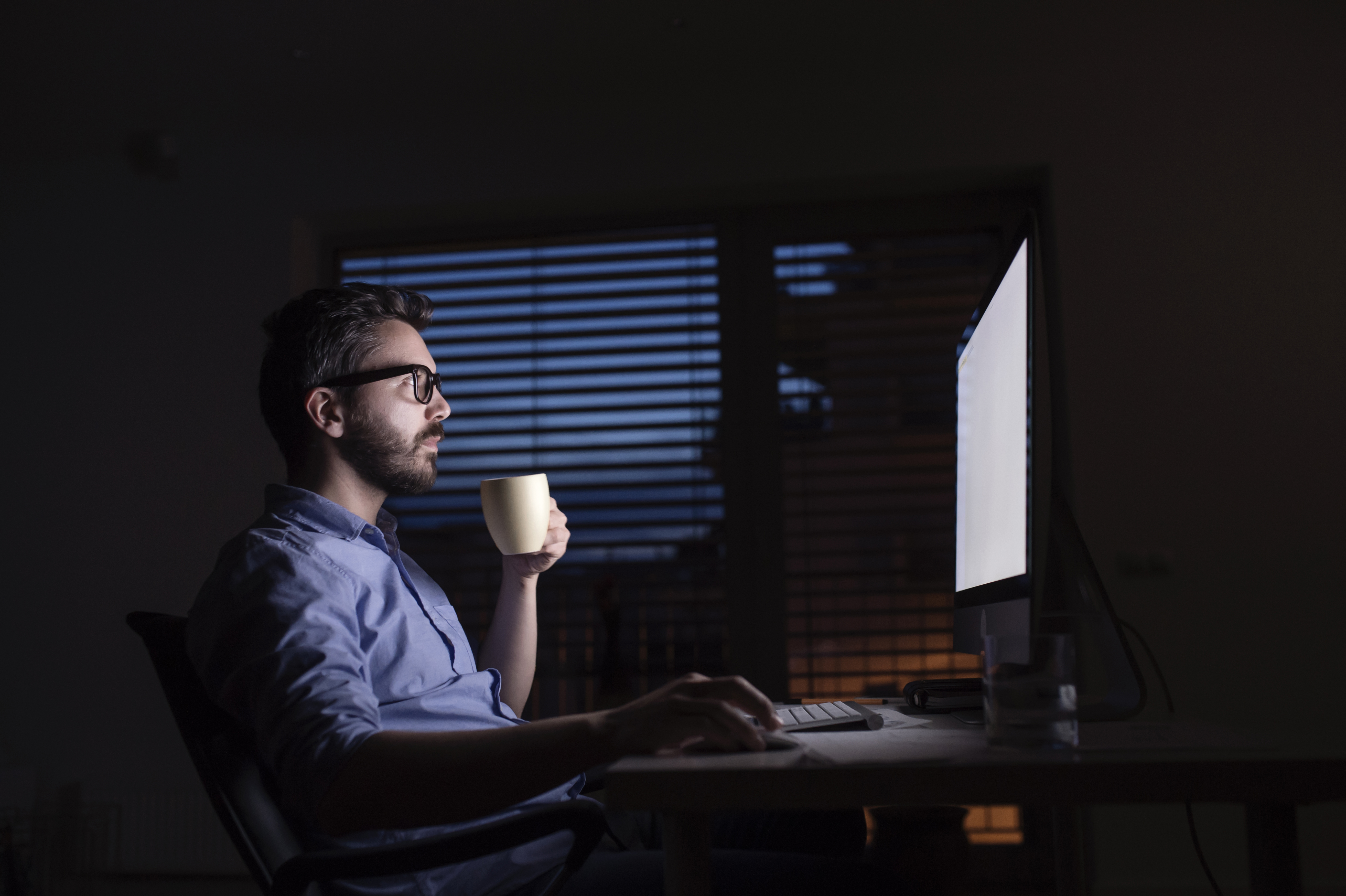 Man working at computer and drinking coffee at night