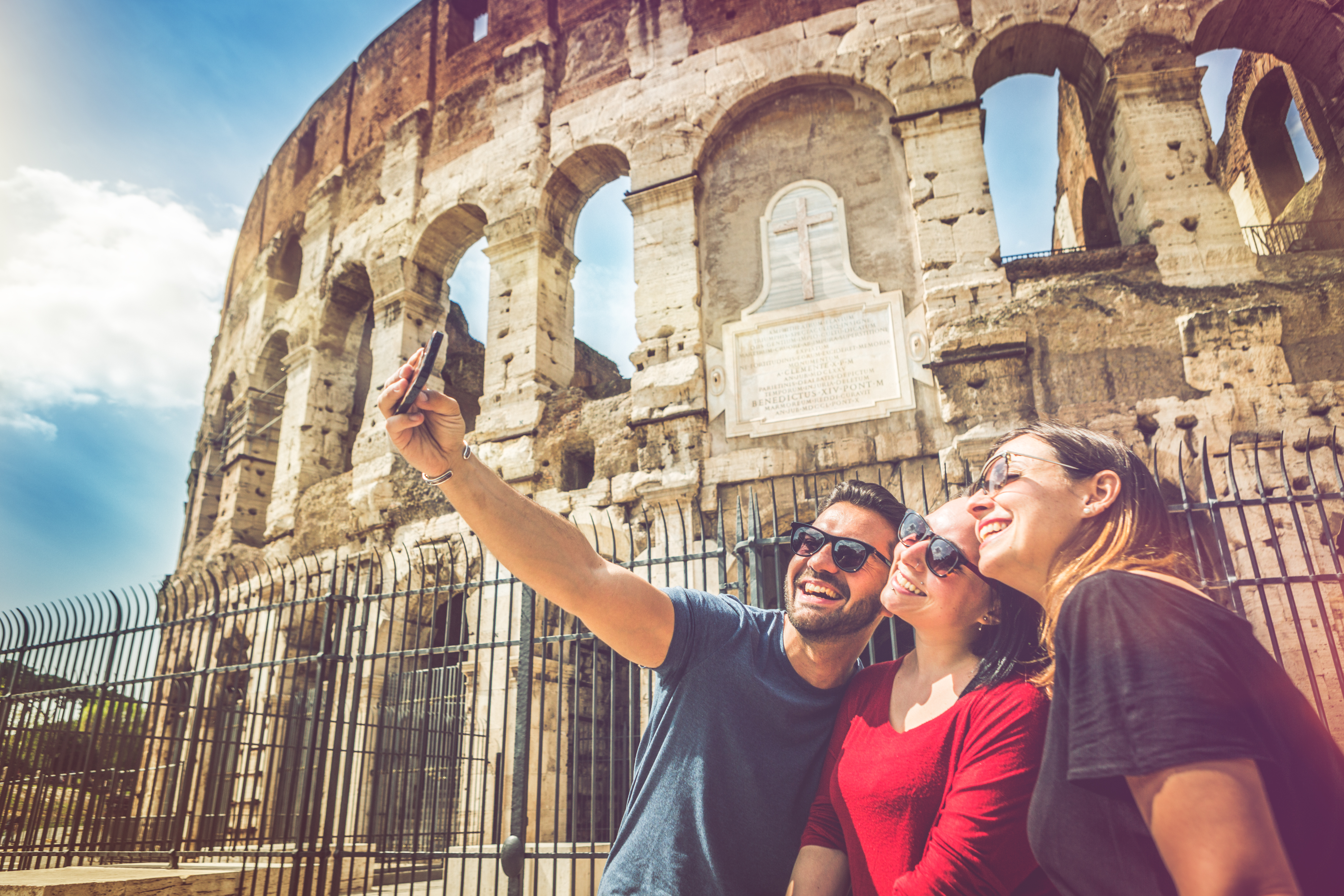 Friends taking a selfie in front of the Coliseum, Rome