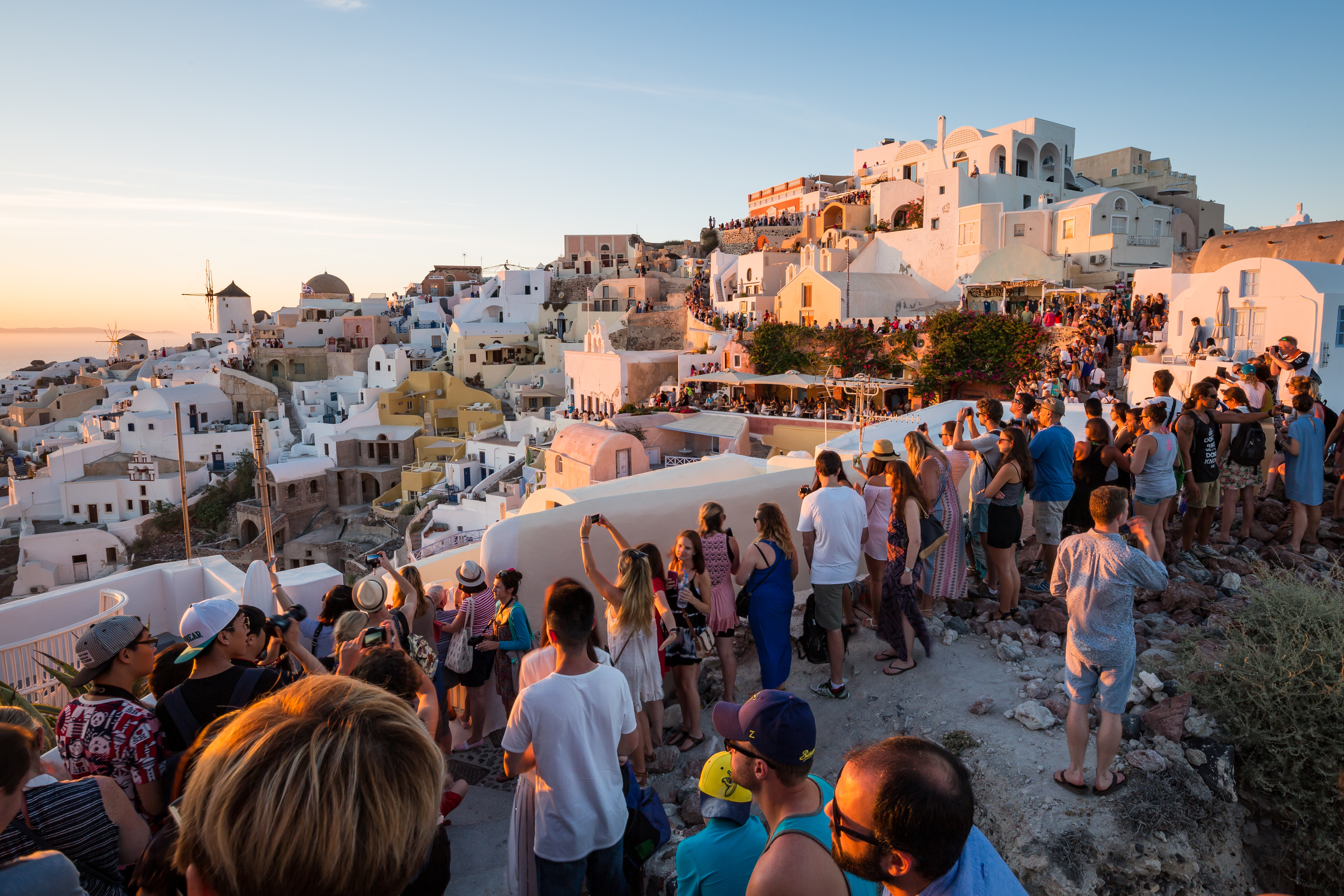 People line the towns walls, for the famous Oia sunset on the Greek island of Santorini, Cyclades, Greek Islands, Greece, Europe