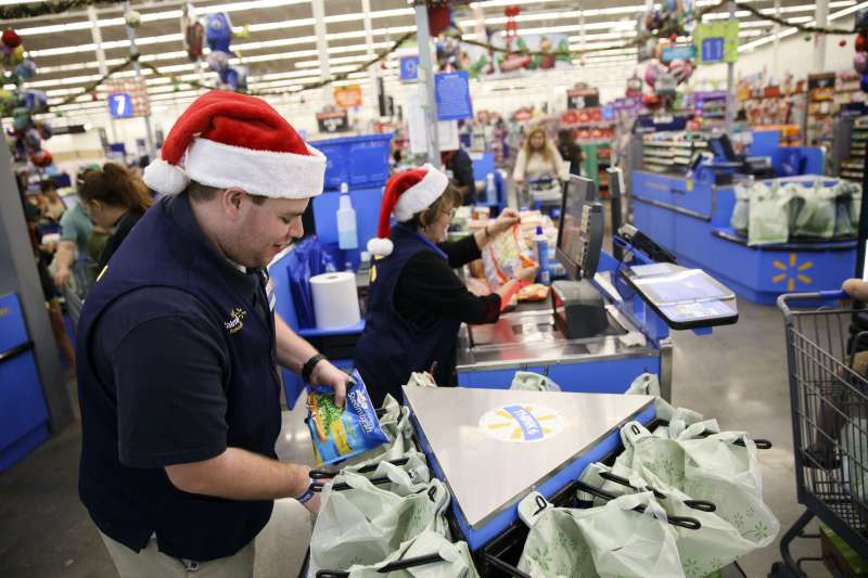 An employee places an item into a shopping bag at a Wal-Mart in Burbank, California, U.S., on Tuesday, Nov. 22, 2016.