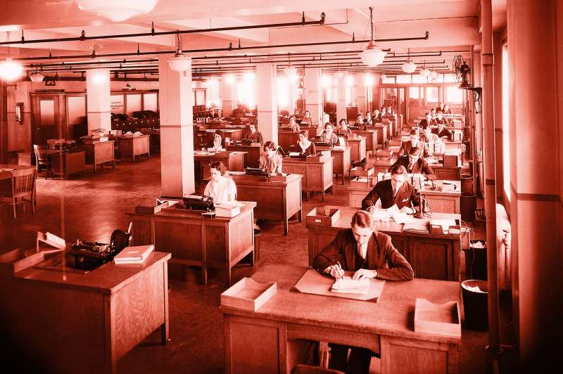 Large business office in New York City, 1930's. There is a row of a dozen men at their desks; next to them are two rows of secretaries.
