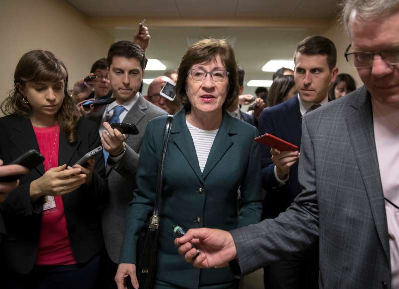 In this Nov. 30, 2017, file photo, with reporters looking for updates, Sen. Susan Collins, R-Maine, and other senators rush to the chamber to vote on amendments as the Republican leadership works to craft their sweeping tax bill in Washington.