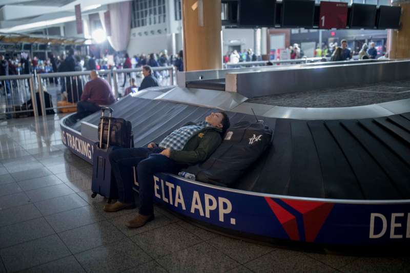 A traveler sleeps on a baggage carousel at Hartfield-Jackson Atlanta International Airport, Sunday, Dec. 17, 2017, in Atlanta.