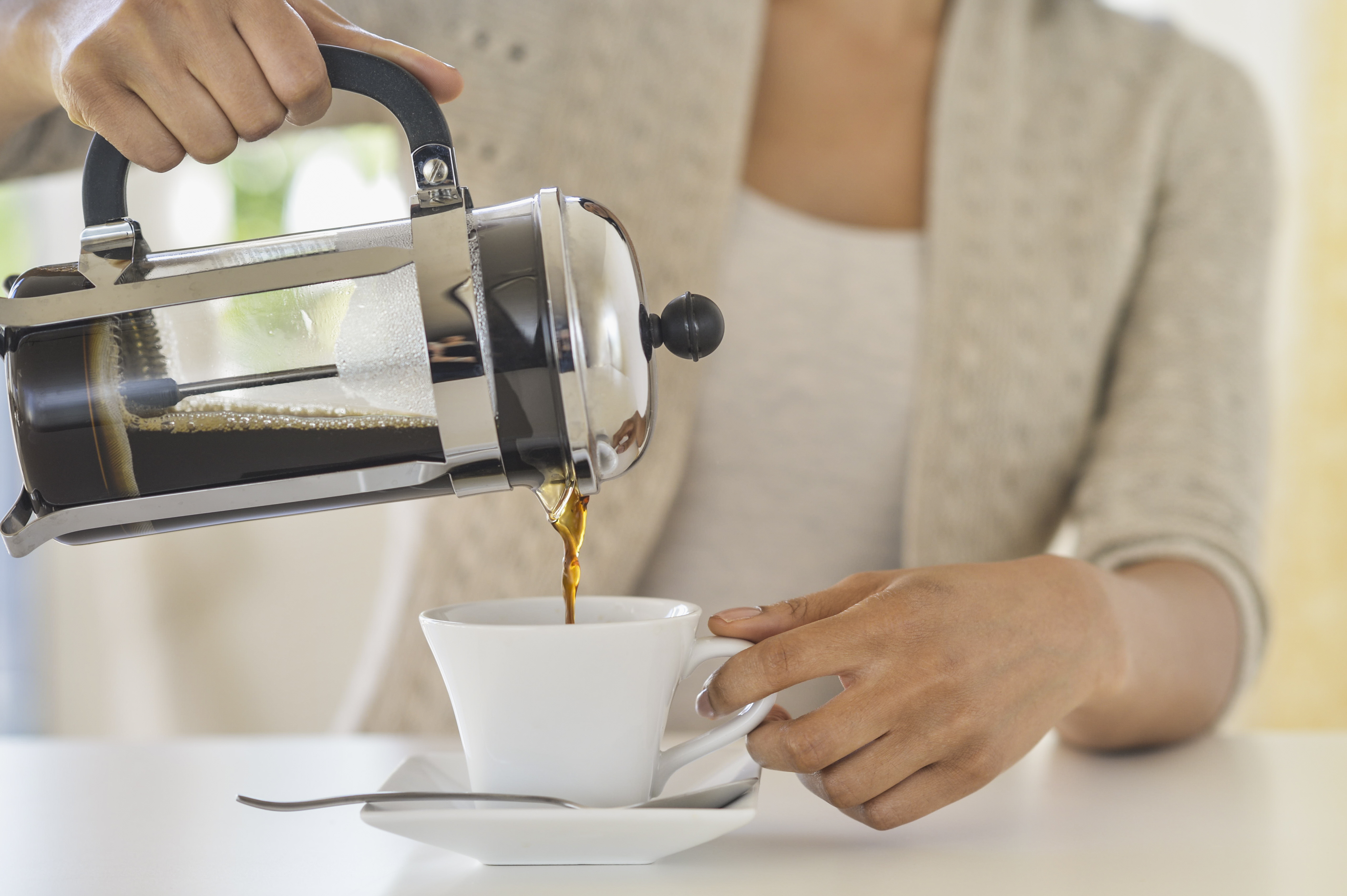 Woman pouring French pressed coffee into a mug in the morning.
