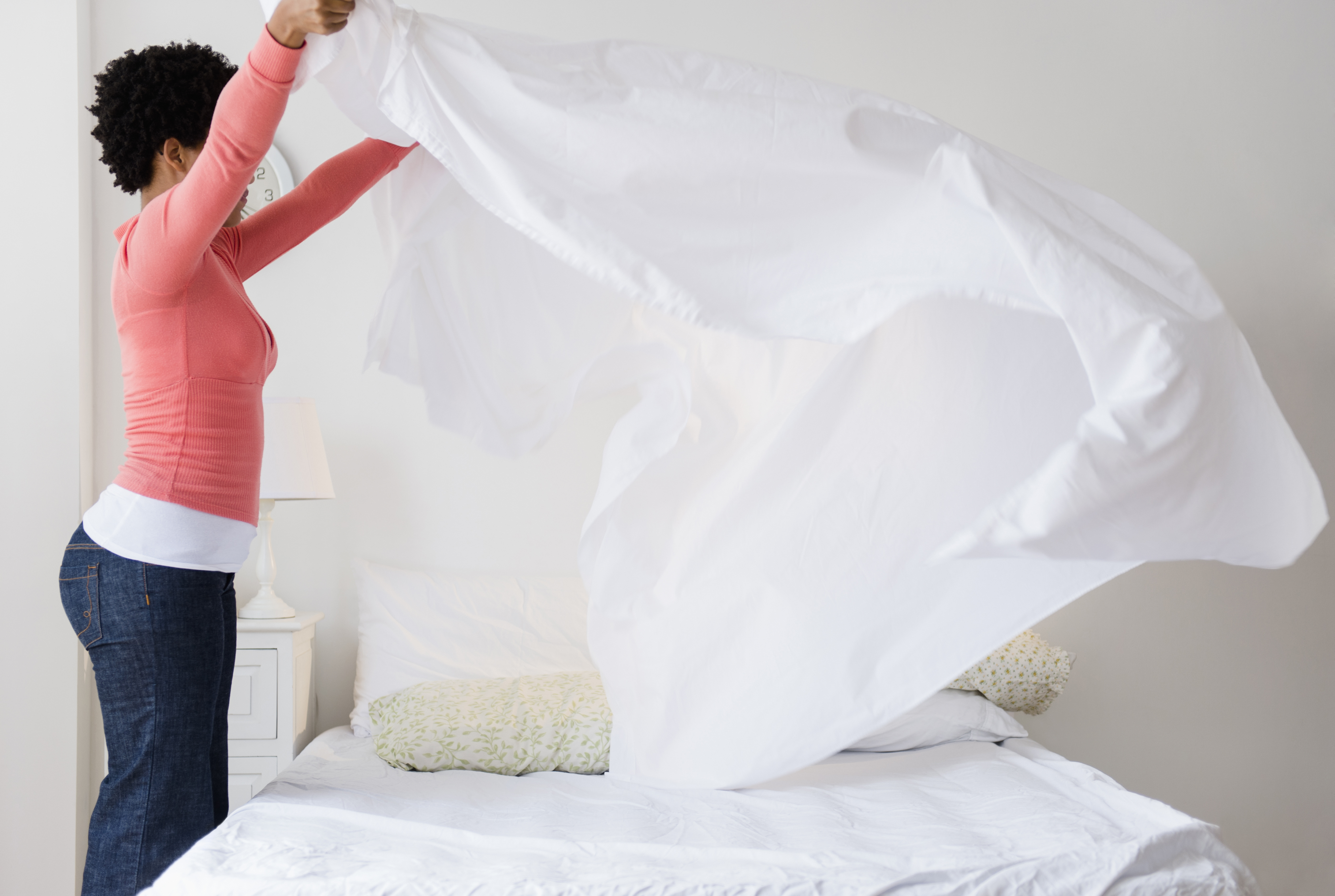 Woman putting clean white sheets on mattress.