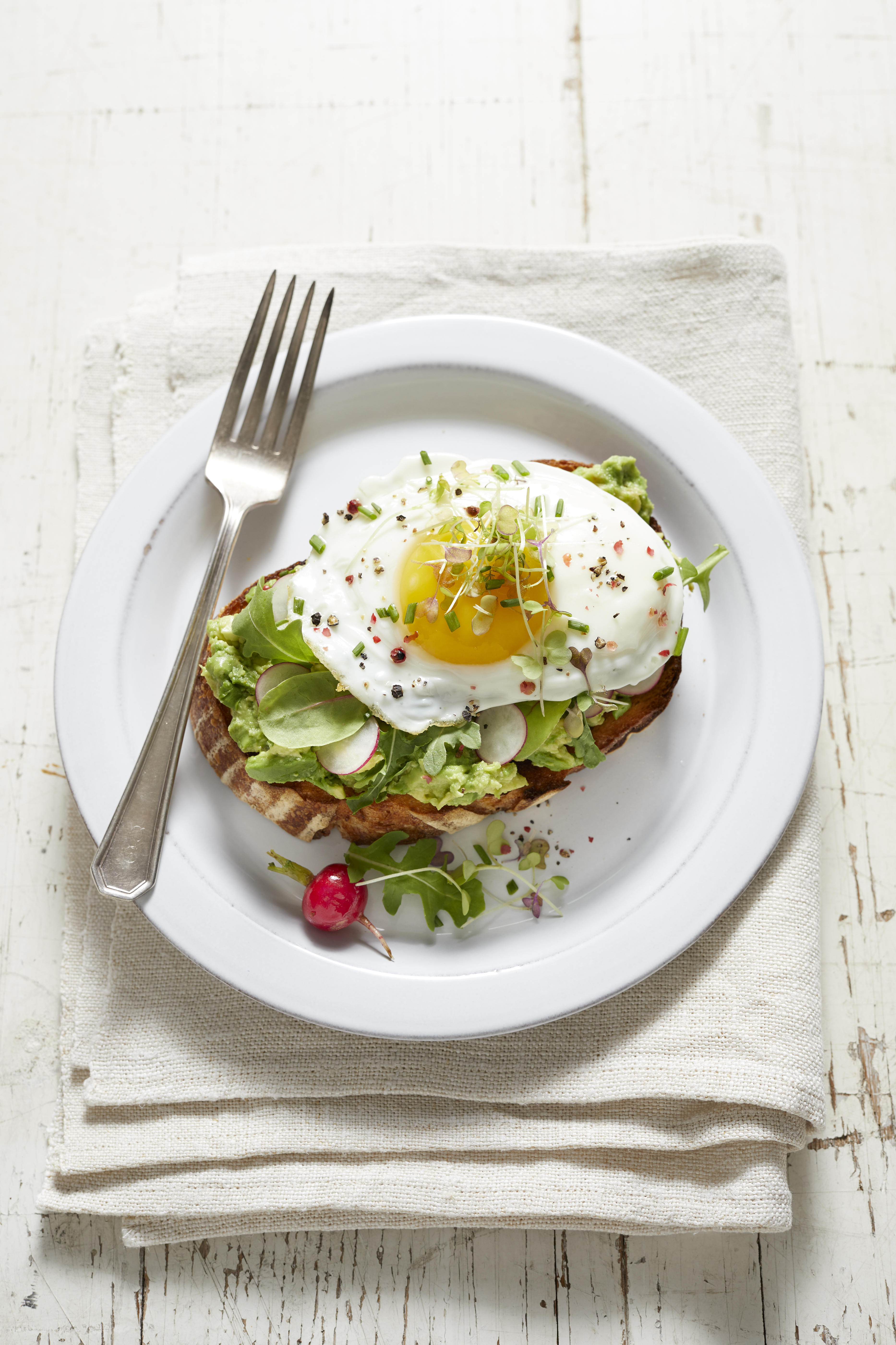 Avocado toast with radish, fried egg and micro greens