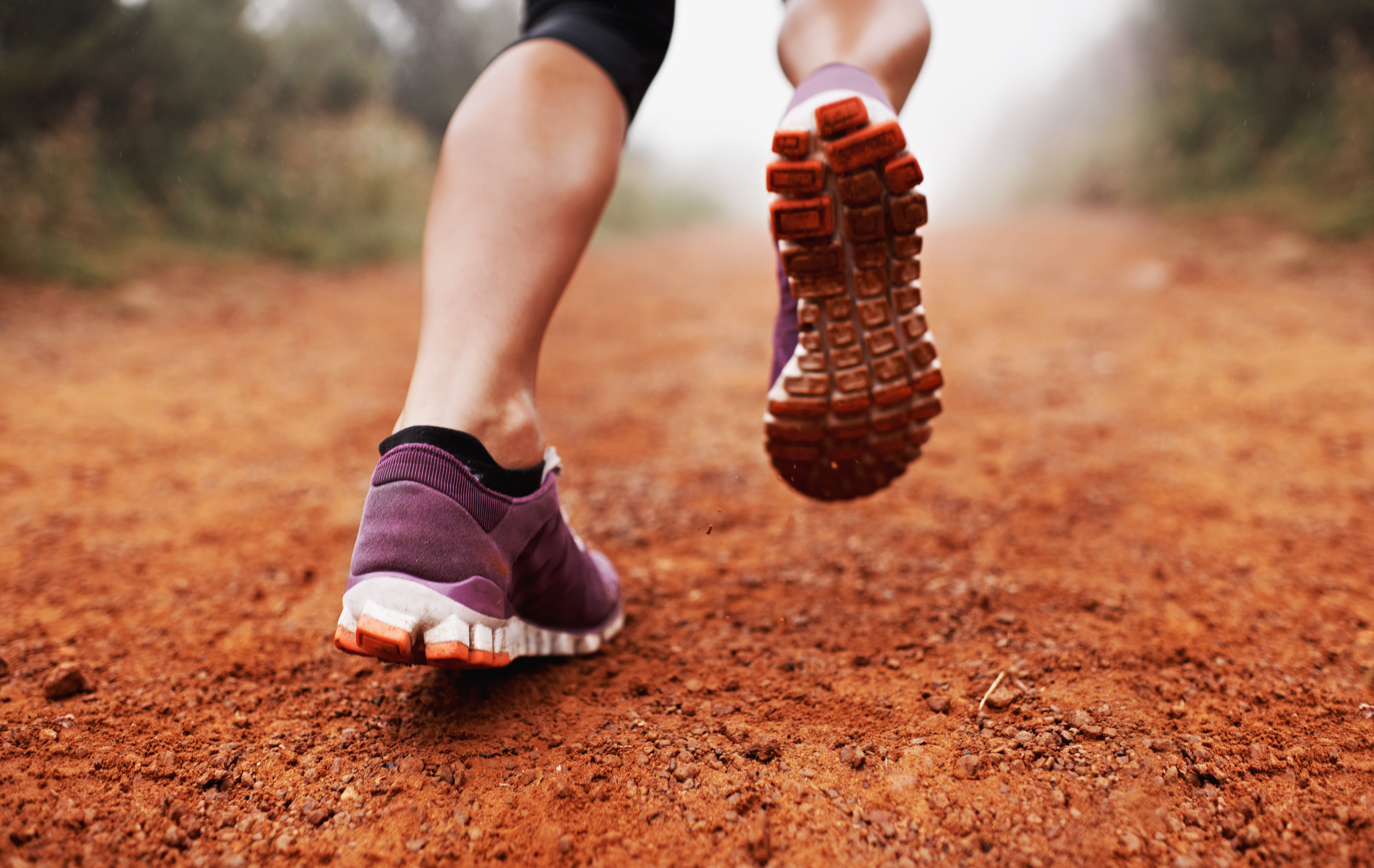 Closeup shot of a woman running on a trail on a misty morning