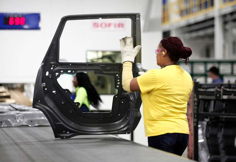 A worker handles a door that came out of the new $63 million press at the Fiat Chrysler Automobiles.