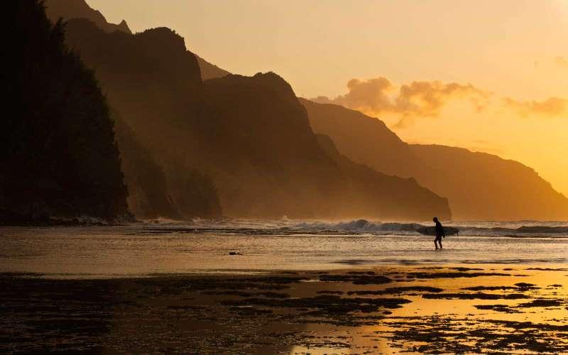 Surfer on the beach and the Na Pali Coast seen from Ke'e beach, Ha'ena, Kauai, Hawaii