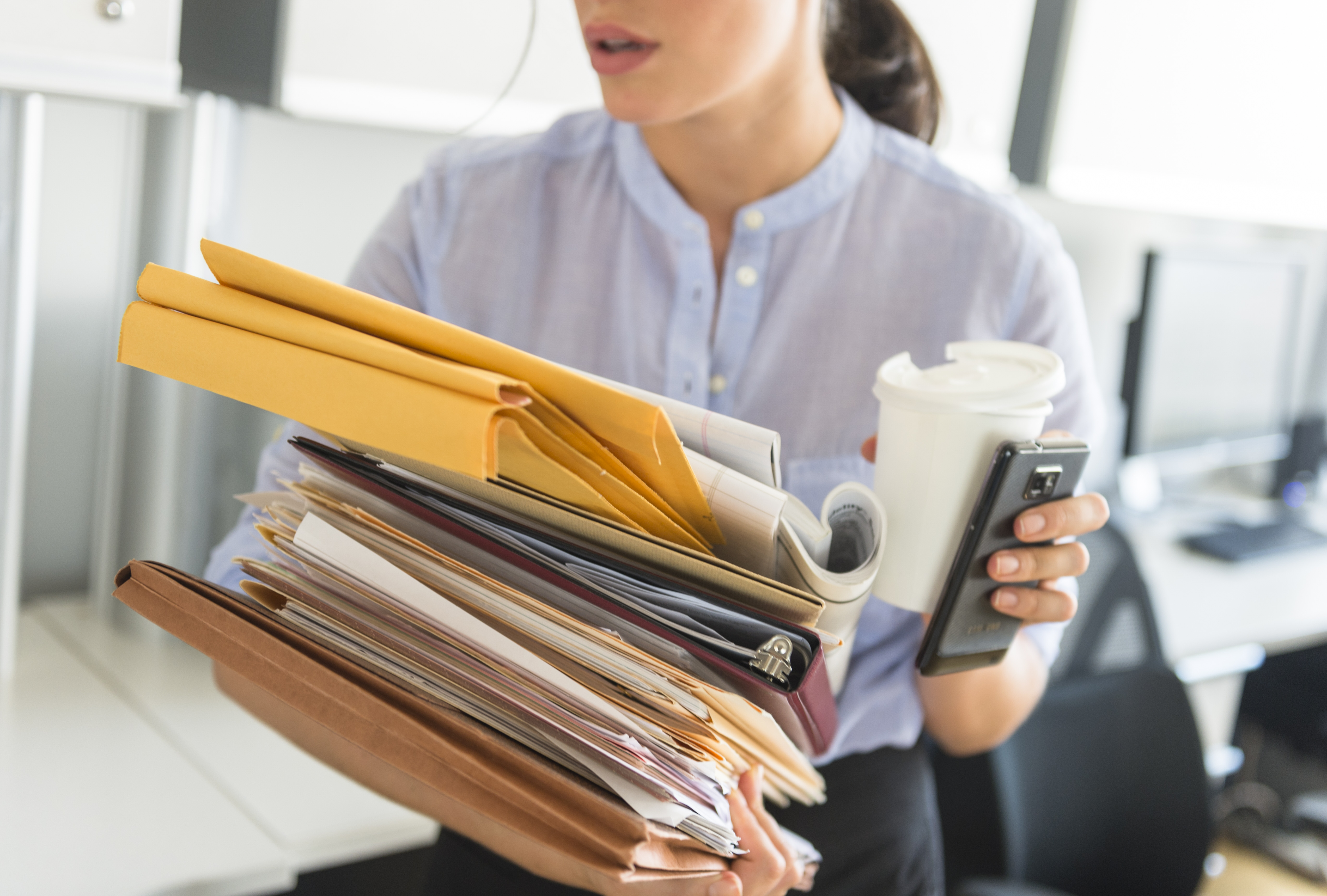 Business woman holding stack of documents in office