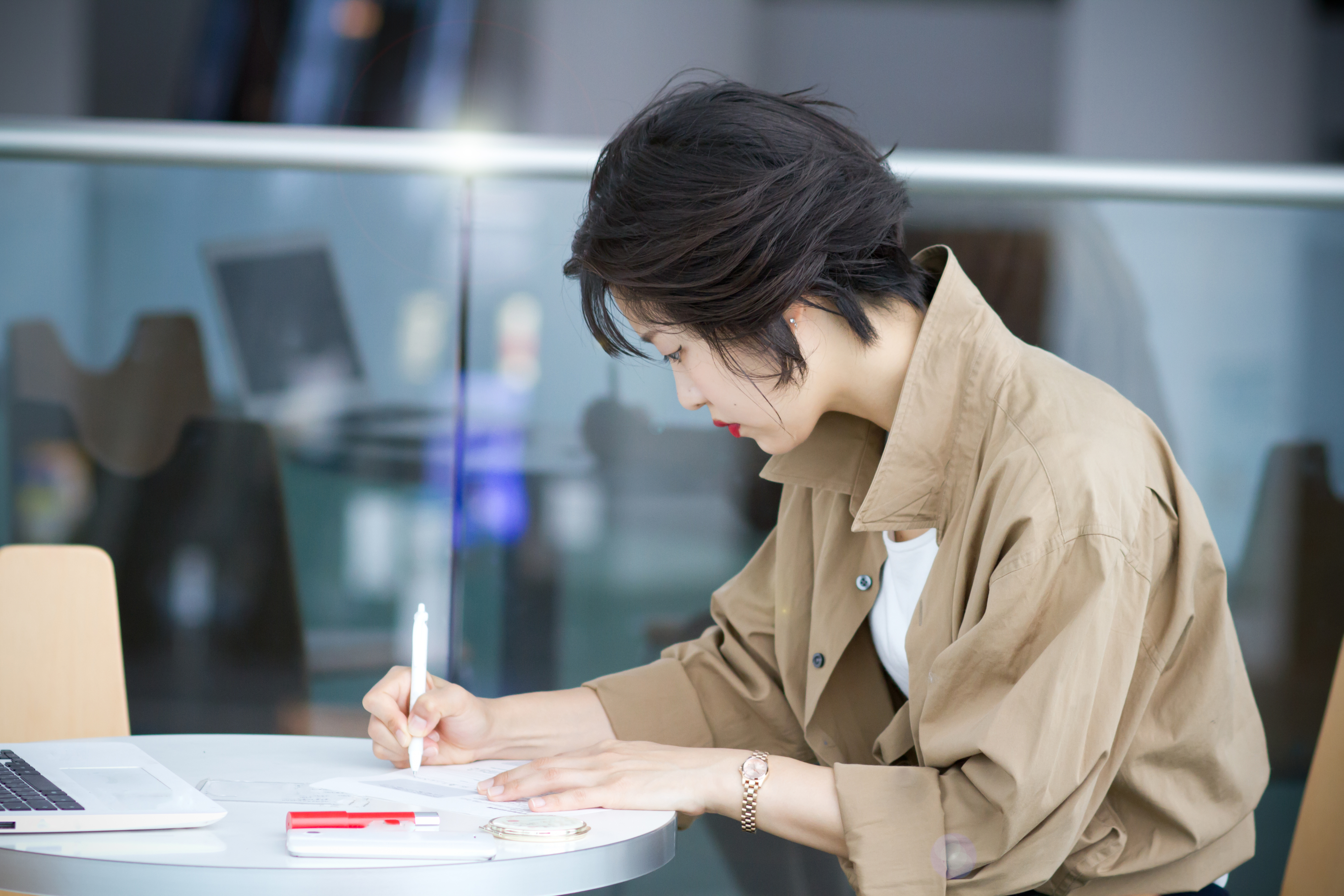 Woman taking notes at her desk.