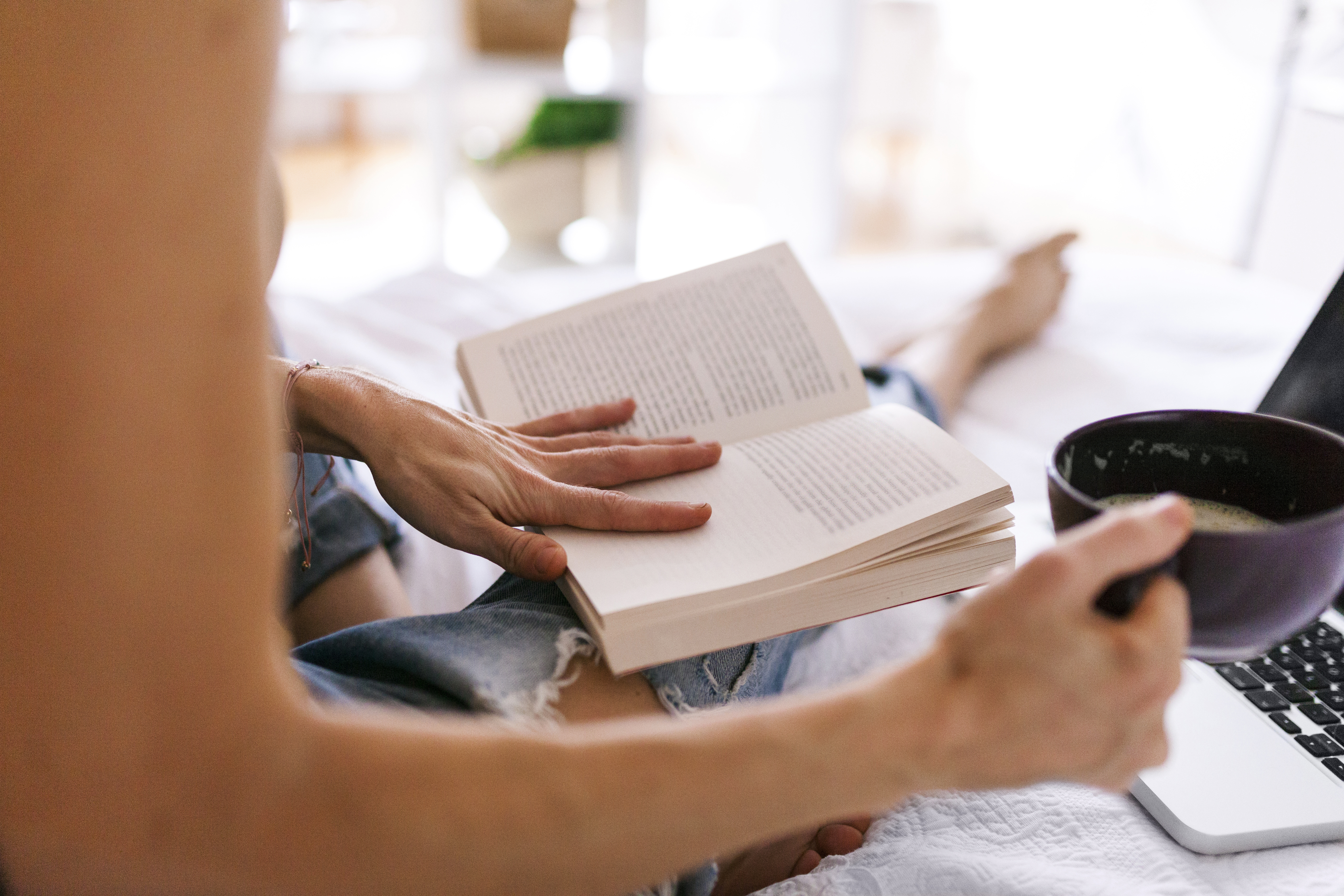 Woman sitting on bed drinking coffee, using laptop and reading book, close up