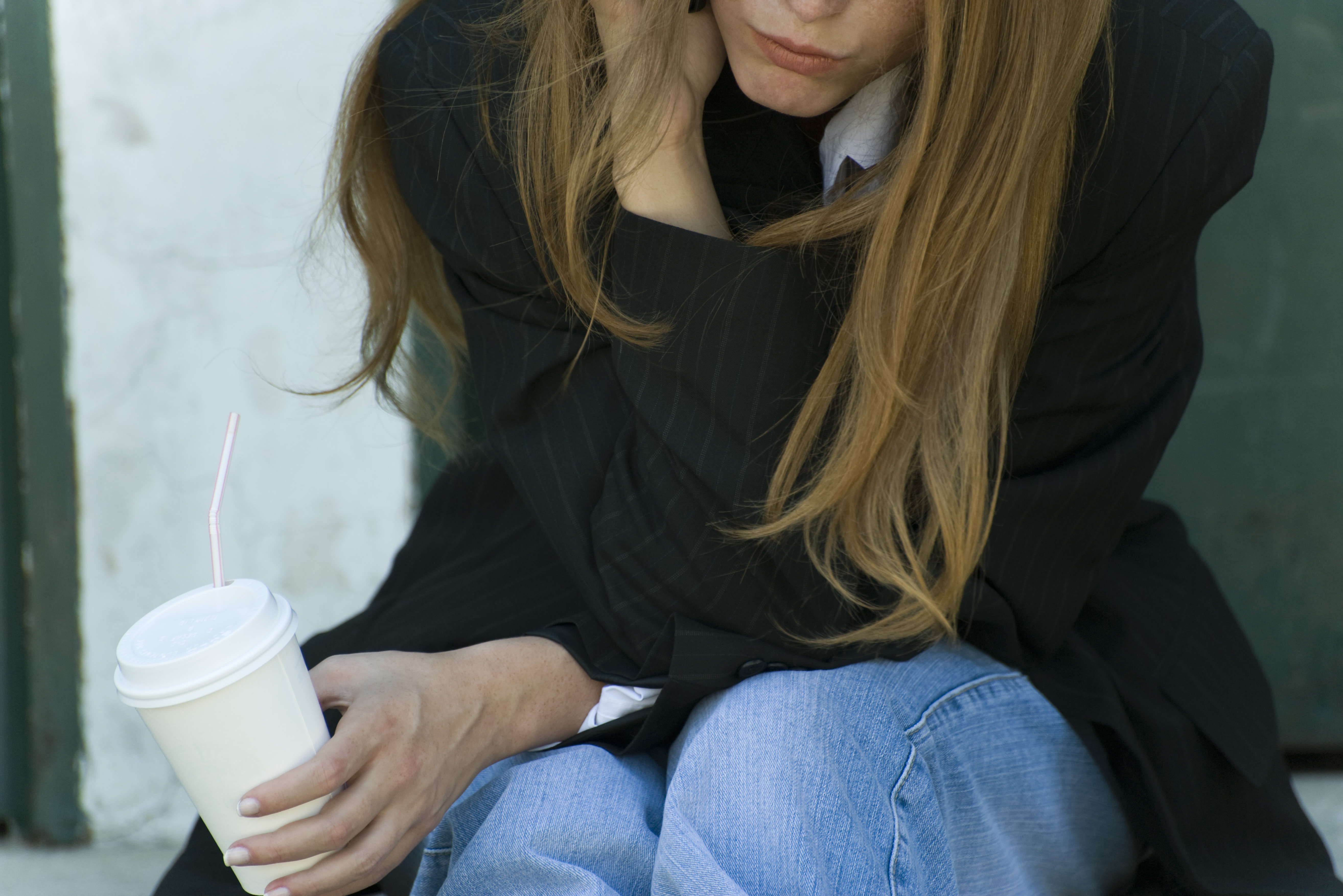 Young woman leaning on elbow, holding cup, cropped view