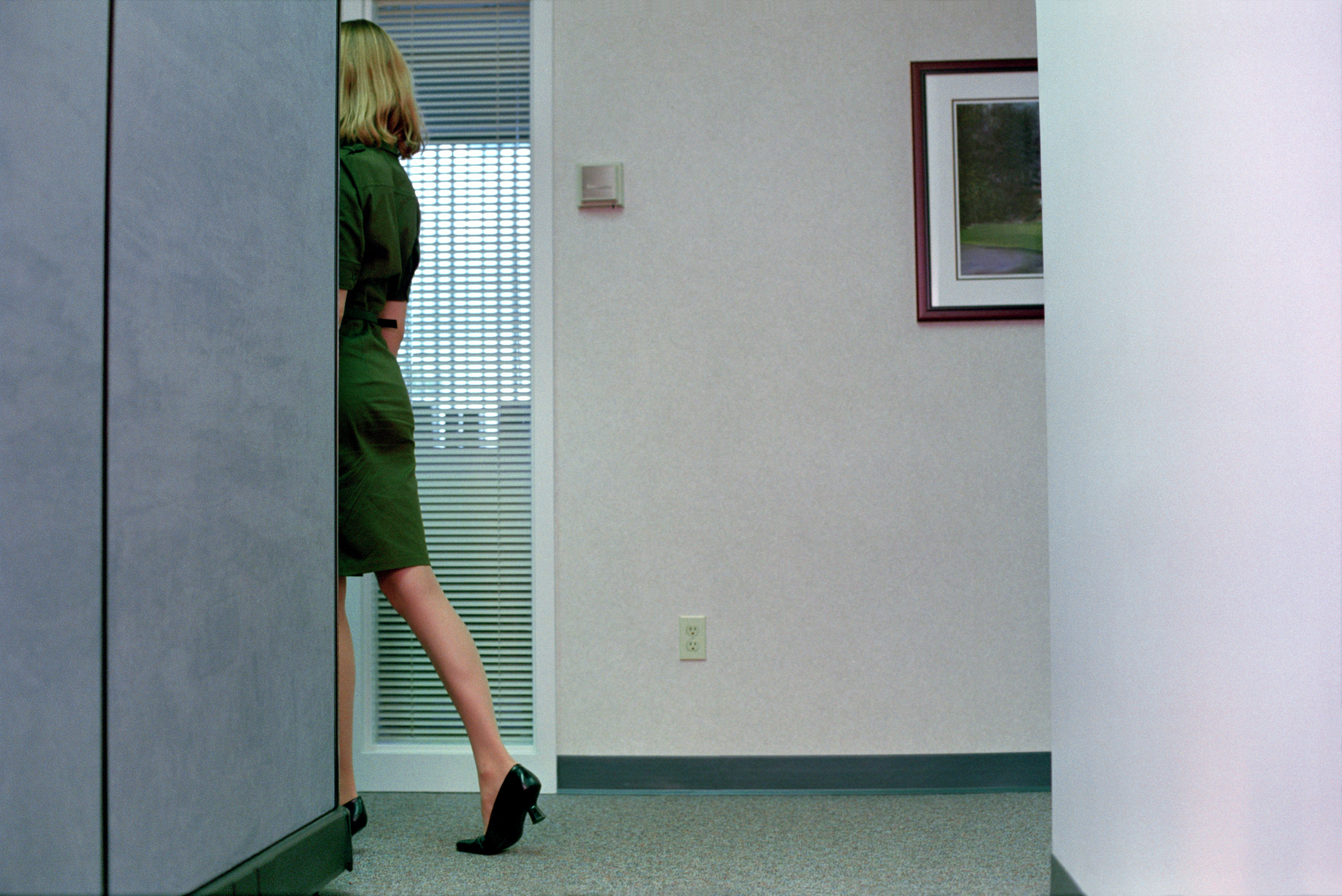 Female office worker turning corner in corridor, rear view
