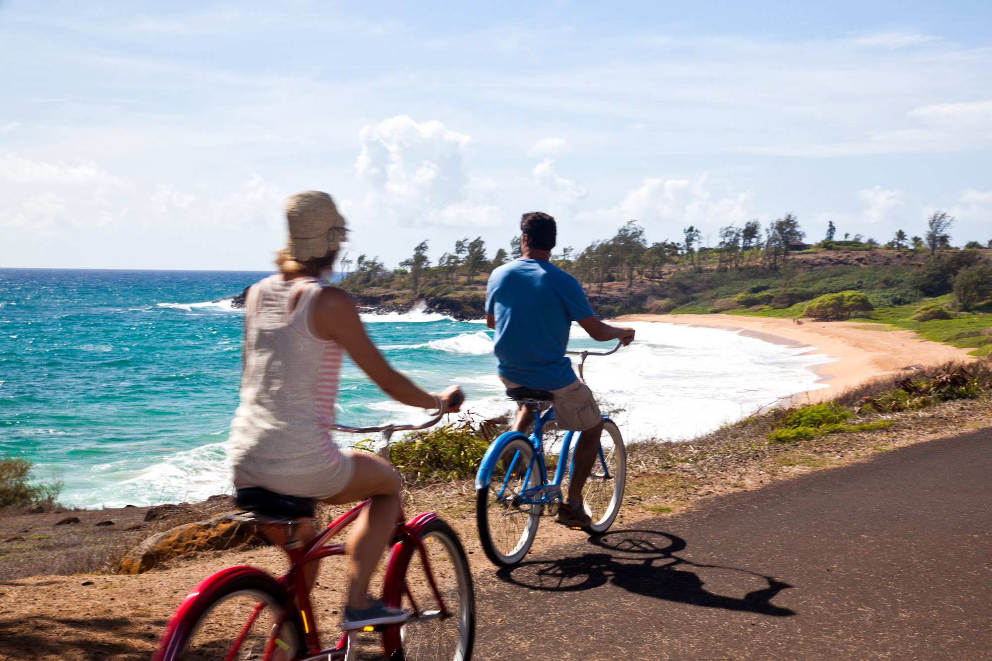 Couple ride on oceanside path. Kapaa Kauai County.