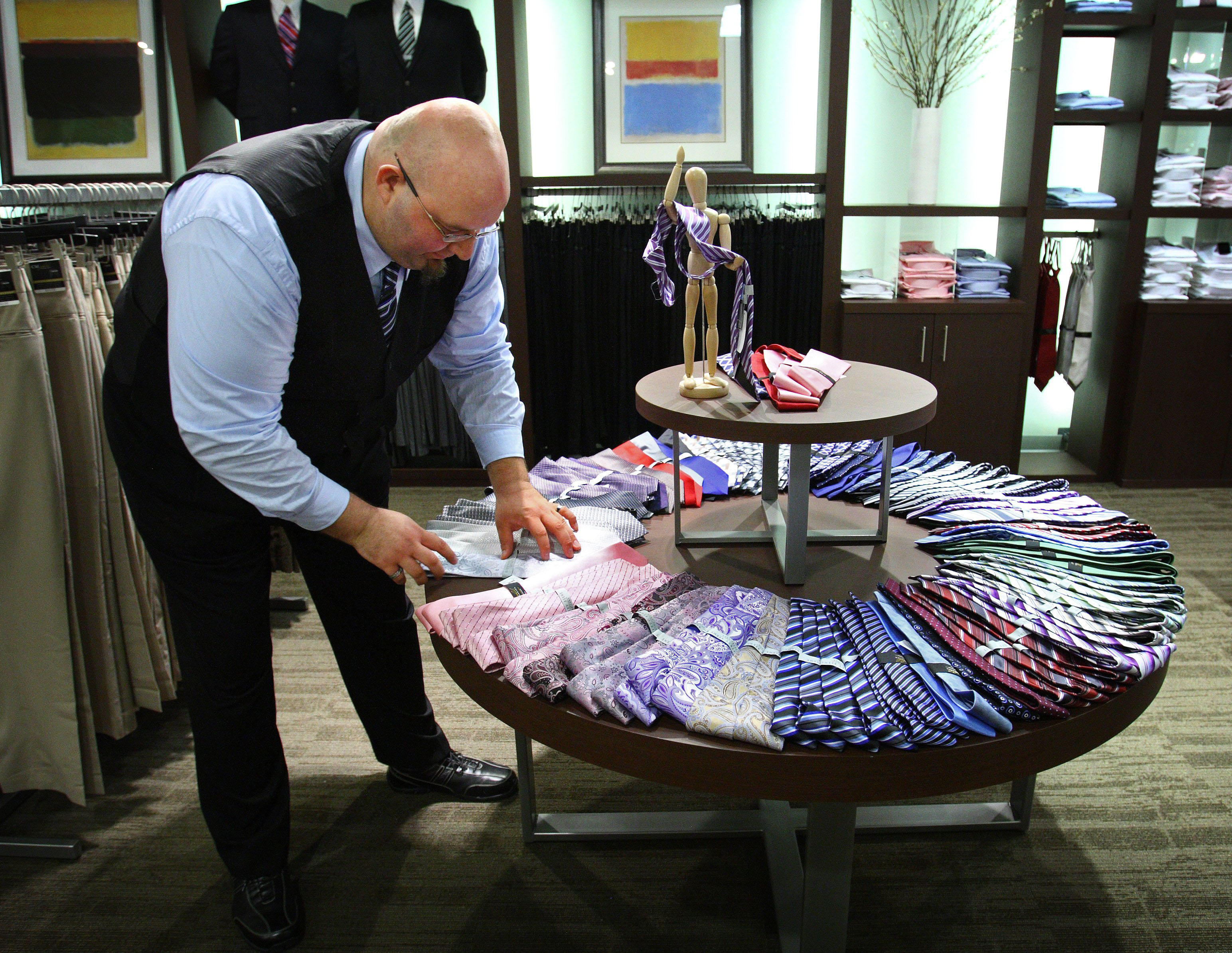 Aug. 05, 2010 - Memphis, TN, U.S. - -August 5, 2010 - Brian Hackney, a Casual Male store manager from Nashville, straightens ties while helping set up the Destination XL store in the East Gate Shopping Center. The new men's superstore concept catering to