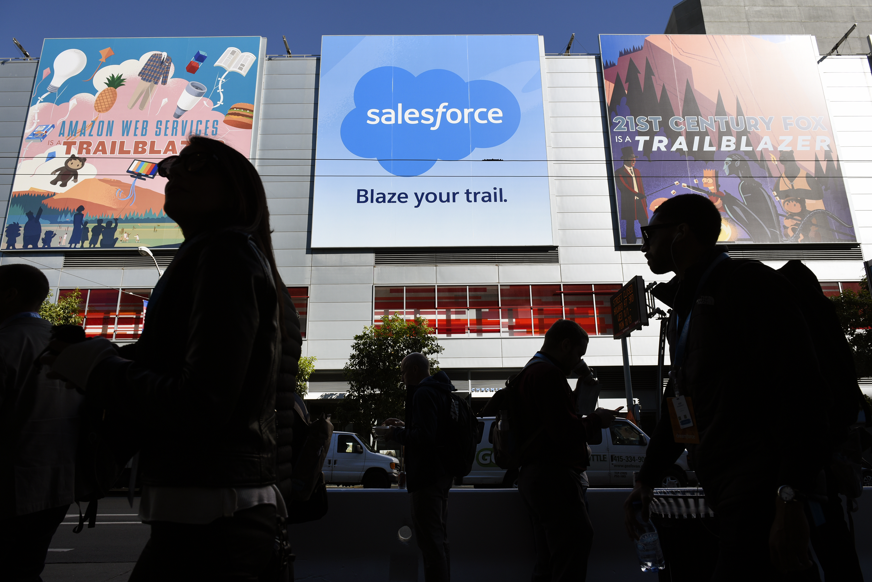 Pedestrians walk past signage for the DreamForce Conference in San Francisco, California, U.S., on Monday, Nov. 6, 2017. Salesforce Chief Executive Officer Marc Benioff -- whose central products help businesses manage customer relationships -- wants to find new ways to encourage greater use of the platforms that enable clients to build software and customize features.