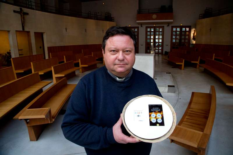 Father Didier Duverne holds a tablet in a collection basket, allowing contactless card payments at the Saint Francois de Molitor church in Paris on Jan.18, 2018