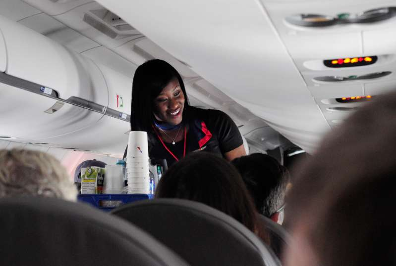 An American Airlines flight attendant serves drinks to passengers after departing from Dallas/Fort Worth International Airport in Texas.