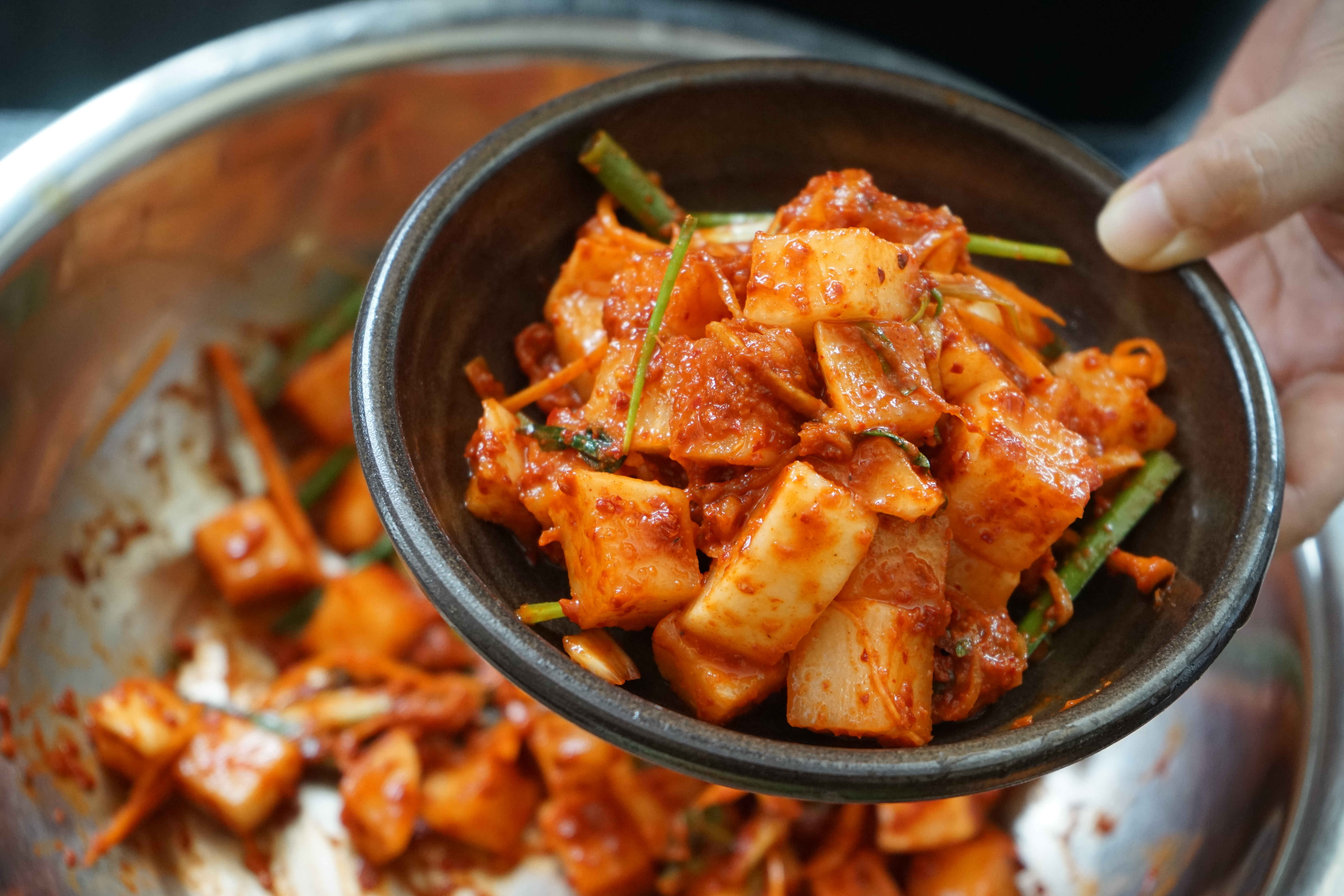 Cropped Image Of Hand Holding Kimchee In Bowl Over Cooking Pan