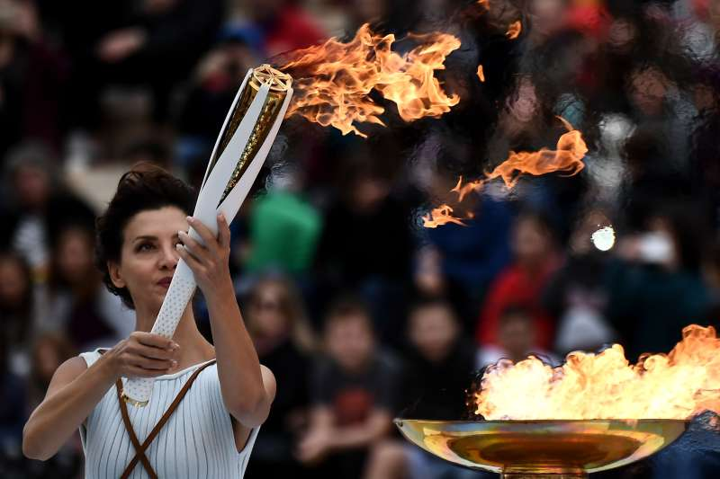 Actress Katerina Lechou, performing a high priestess lights a torch at The Panathenaic Stadium in Athens on October 31, 2017, during the handover ceremony of the Olympic flame for the 2018 Winter Olympics in Pyeongchang, South Korea.