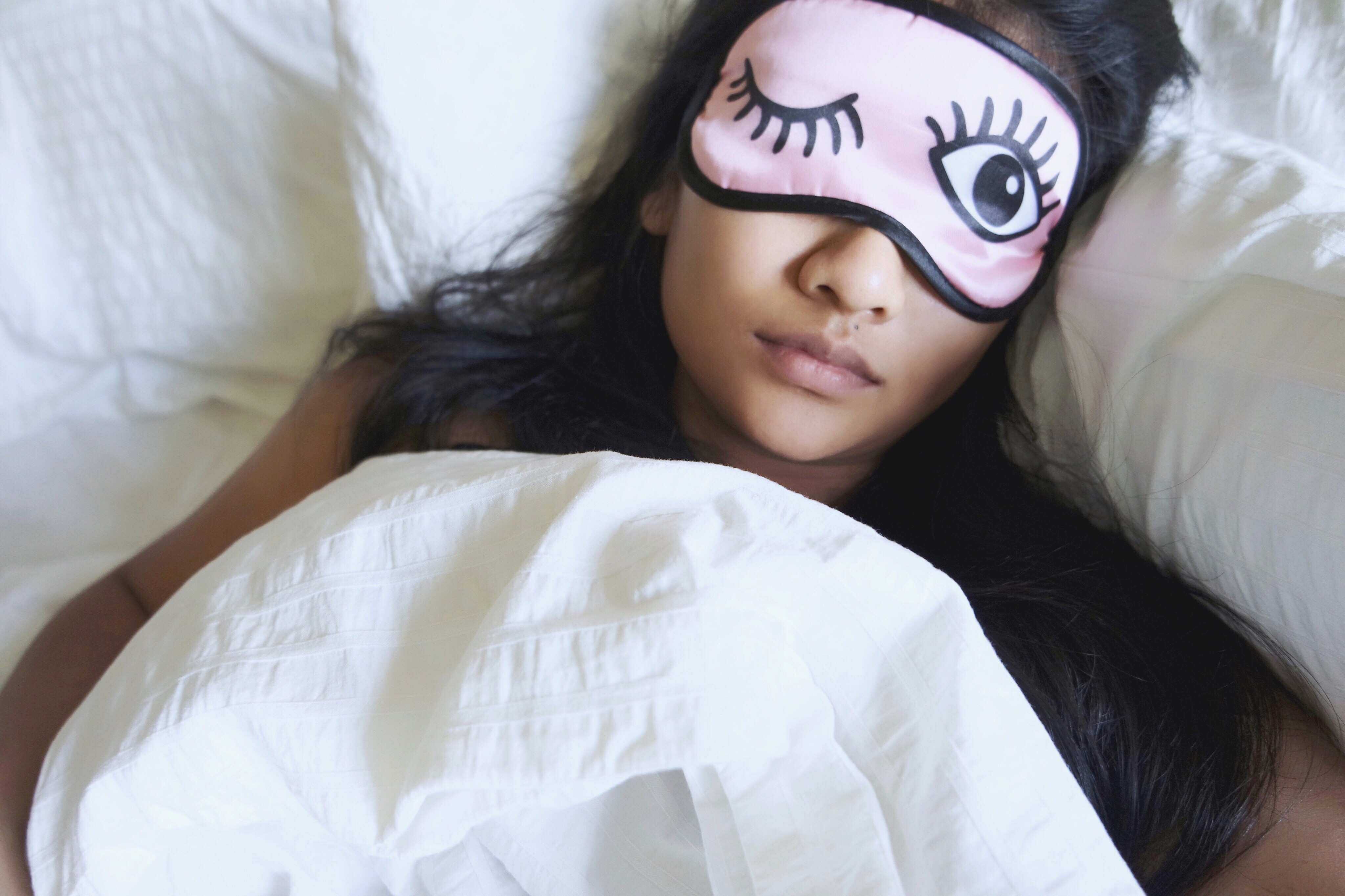 High Angle View Of Woman Wearing Eye Mask While Sleeping In Bed