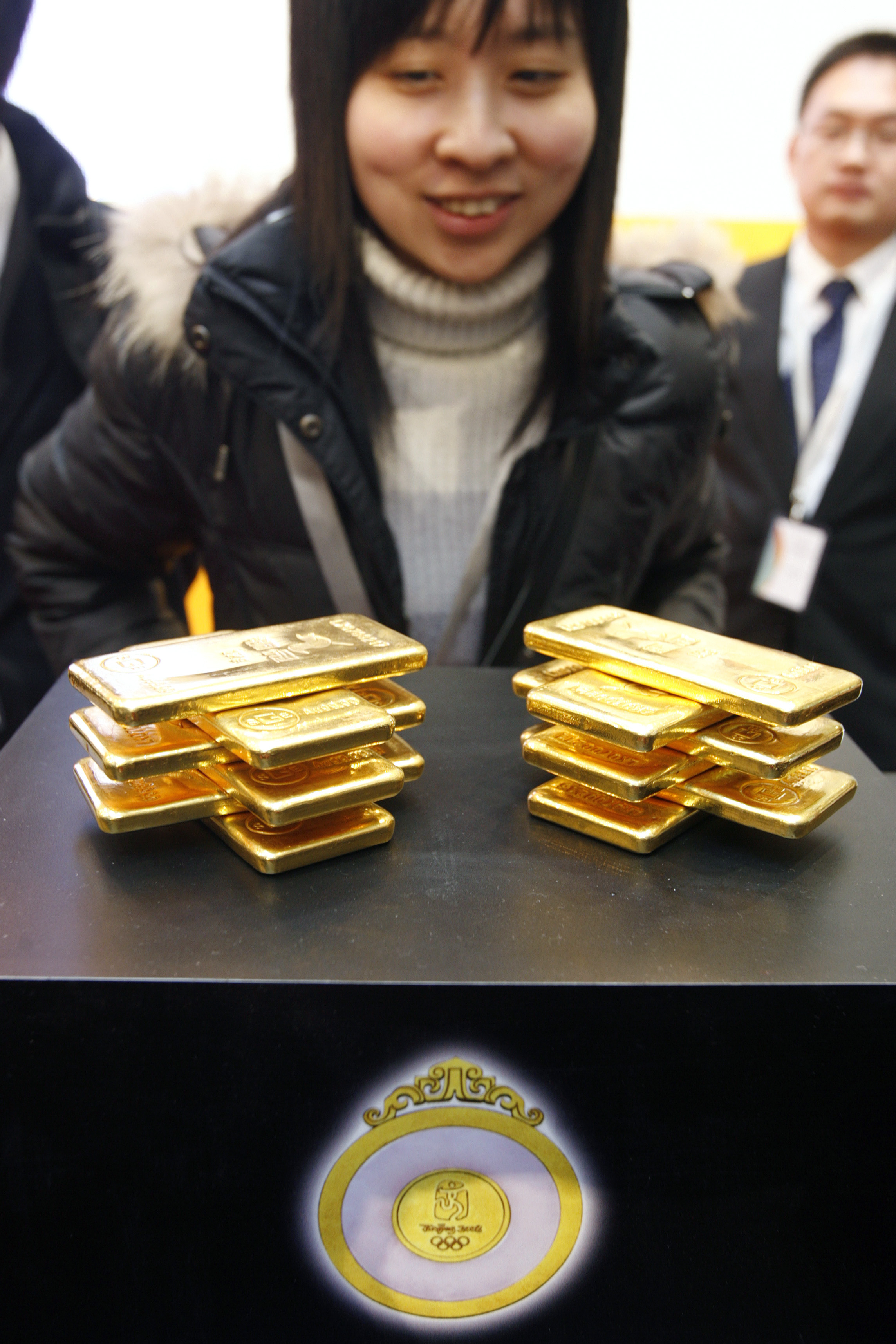 A woman looks at gold bars during a handover ceremony in Shanghai