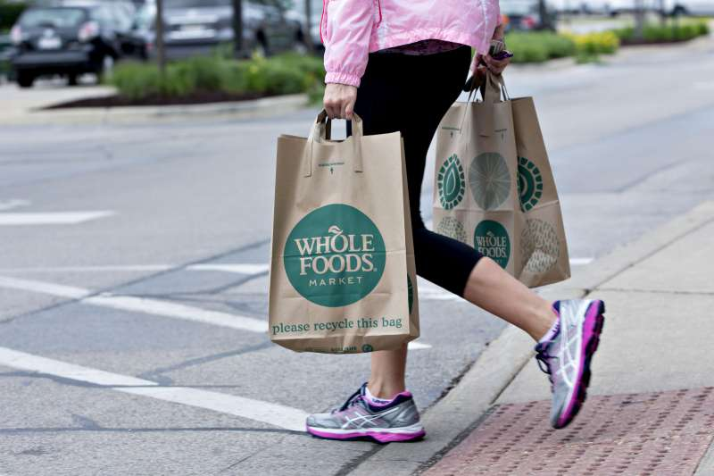 A customer carrying shopping bags exits a Whole Foods Market Inc. location in Naperville, Illinois, U.S., on Friday, June 16, 2017.