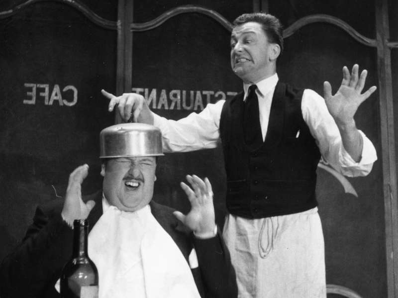 An irate waiter hitting a diner over the head with a saucepan, in a scene from the Paris revue 'La Plume de ma Tante' at London's Garrick Theatre.  Original Publication: Picture Post - 8179 -  It's The New French Line - pub. 1955   (Photo by Thurston Hopkins/Getty Images)
