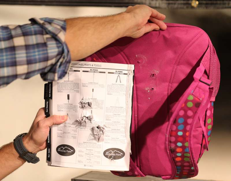 A book and the back of a child's bulletproof backpack are displayed with the effects of bullets that were shot through it without Amendment II's Rynohide CNT Shield on December 21, 2012 in Salt Lake City, Utah.