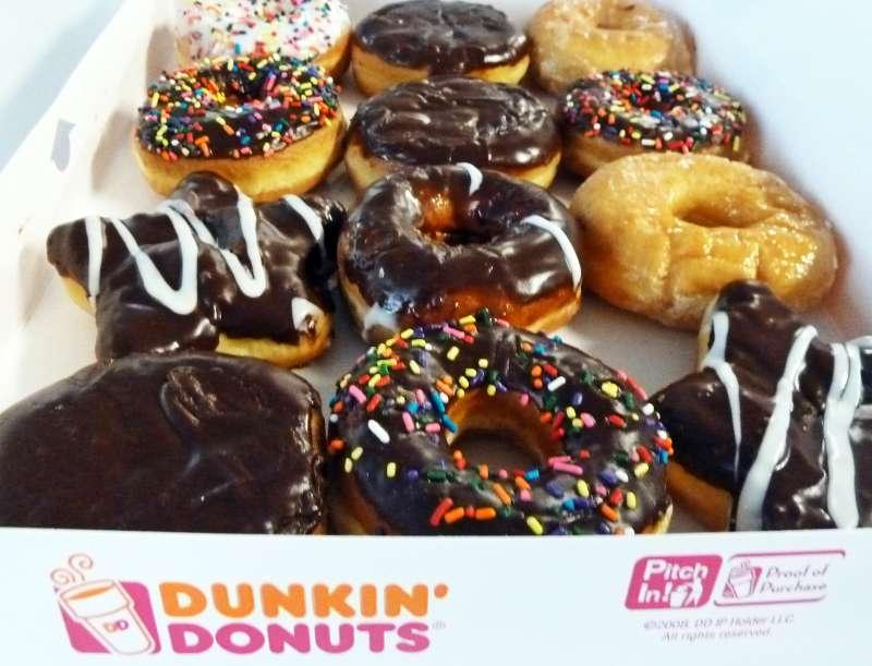 An assortment of Dunkin' Donuts ring doughnuts and filled doughnuts, glazed doughnuts and powdered doughnuts is seen in a paper box in Washington, DC June 5, 2015.